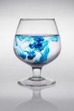 Verre avec l'encre bleue qui crée des vagues de la création de couleur des vagues colorées Image libre de droits
