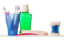 Verre avec la brosse à dents, rasoir jetable, pâte dentifrice, élixir, tampons de coton Images stock
