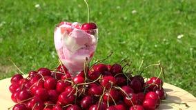Verre avec la crème glacée et la baie de cerise sur le dessus dans le jardin clips vidéos