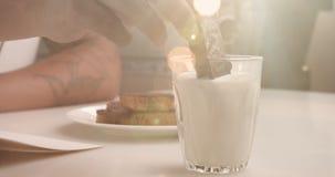 Verre avec la main du ` s de lait et d'homme avec le biscuit Obtenez le biscuit humide en lait clips vidéos