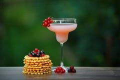 Verre avec le cocktail et les gaufres roses sur le bokeh vert de fond Photo stock