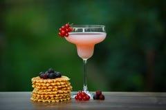 Verre avec le cocktail et les gaufres roses sur le bokeh vert de fond Photographie stock