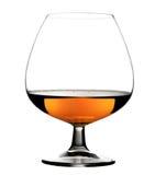 Verre avec le cognac sur le fond blanc d'isolement Photographie stock libre de droits