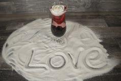 Verre avec le lettrage rose et d'amour dans le sable Photographie stock libre de droits
