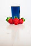 Verre avec le thé et les fraises thaïlandais bleus froids Photographie stock libre de droits