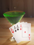 Verre avec un cocktail et des cartes de jouer Fond en bois Images stock