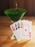 Verre avec un cocktail et des cartes de jouer Fond en bois Photo libre de droits