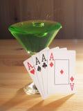 Verre avec un cocktail et des cartes de jouer Fond en bois Image stock