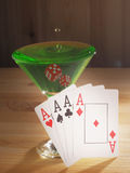 Verre avec un cocktail et des cartes de jouer Fond en bois Photographie stock