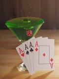 Verre avec un cocktail et des cartes de jouer Fond en bois Images libres de droits