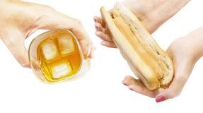 Verre avec une boisson et une saucisse dans la pâte dans les mains photos stock
