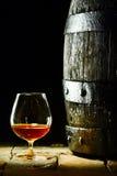 Verre ballon de cognac et un vieux baril de chêne Image stock