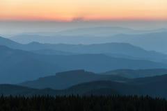Verre bergketen en dunne laag wolken op de valleien Stock Foto