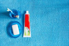 Verre bleu avec les brosses à dents, le tube de la pâte dentifrice et le porte-savon W Image stock