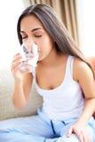 Verre à boire de femme de l'eau se penchant en avant Photographie stock libre de droits