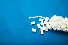 Verre cassé avec des cubes en sucre sur un fond bleu, l'espace vide pour le texte images stock