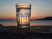 Verre d'eau au coucher du soleil Photo stock