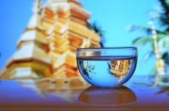 Verre d'eau avant un temple Photos libres de droits