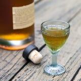 Verre d'eau-de-vie fine de vintage avec la bouteille et le liège Image stock