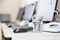 Verre d'eau sur le bureau au centre d'appels Images stock
