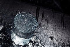 Verre d'eau sur une table humide photo stock