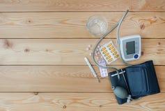 Verre d'eau, tonometer, thermomètre, et médicaments Photographie stock libre de droits