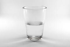 Verre d'isolat avec de l'eau demi. Photographie stock libre de droits