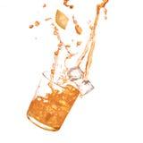 Verre d'orangeade froide avec l'éclaboussure de l'eau et les glaçons photographie stock libre de droits
