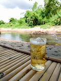 Verre de bière avec de la glace sur la table en bambou Photo stock