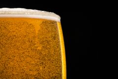 Verre de bière avec des bulles sur le fond noir Images libres de droits