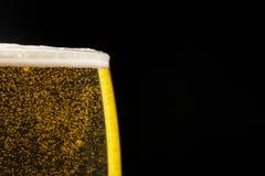 Verre de bière avec des bulles sur le fond noir Photos libres de droits