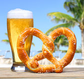 Verre de bière avec le bretzel allemand au-dessus de la vue de plage avec des paumes. Photo libre de droits