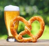 Verre de bière avec le bretzel allemand sur le Tableau en bois au-dessus de la nature Photos libres de droits
