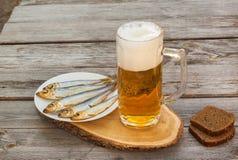 Verre de bière avec un casse-croûte sur une table en bois photographie stock