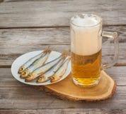 Verre de bière avec un casse-croûte sur une table en bois image stock