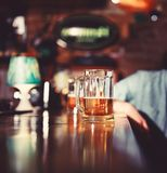 Verre de bière blonde sur le compteur en bois de barre image stock