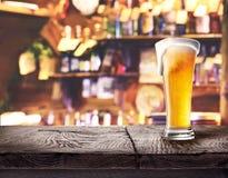 Verre de bière blonde sur le conseil en bois photo stock