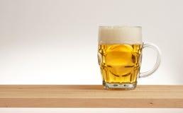 Verre de bière blonde sur un conseil en bois images stock