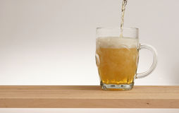 Verre de bière blonde sur un conseil en bois photo stock