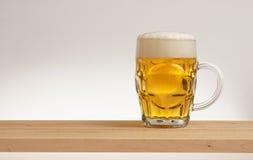 Verre de bière blonde sur un conseil en bois photographie stock