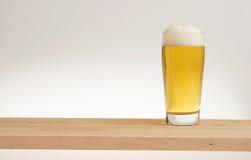 Verre de bière blonde sur un conseil en bois image libre de droits