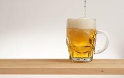 Verre de bière blonde sur un conseil en bois photographie stock libre de droits