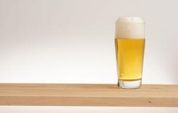 Verre de bière blonde sur un conseil en bois photos libres de droits