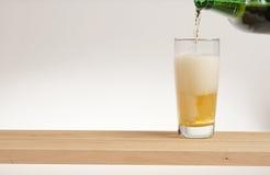 Verre de bière blonde sur un conseil en bois images libres de droits