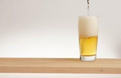 Verre de bière blonde sur un conseil en bois image stock