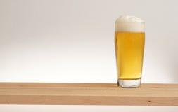 Verre de bière blonde sur un conseil en bois photo libre de droits