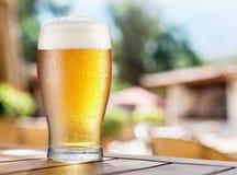 Verre de bière blonde sur une table en bois photo stock