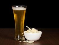 Verre de bière et de calmars salés dans une cuvette Photos stock