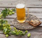 Verre de bière et de pain brun avec des esprots sur une table en bois photo libre de droits