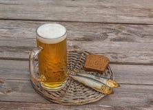 Verre de bière et de poissons fumés sur une table en bois images libres de droits